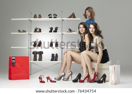 three young women sitting trying shoes looking happy - stock photo