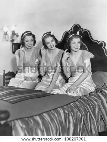Three young women winking - stock photo