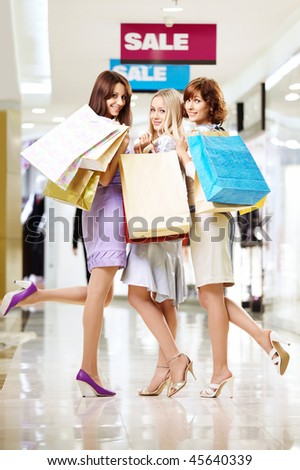 Three young women with bags walk in shop - stock photo