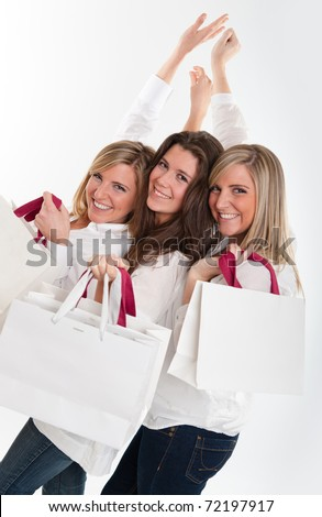 Three young women with happy expressions holding lots of shopping bags - stock photo