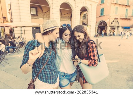 Three young women with smart phone in the city, talking and smiling. This is a mixed race group, one girl is half asian and one is middle eastern. Lifestyle, friendship and urban life concepts.