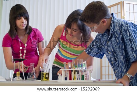 Three youngsters working together on what appears to be a science or chemistry project. - stock photo