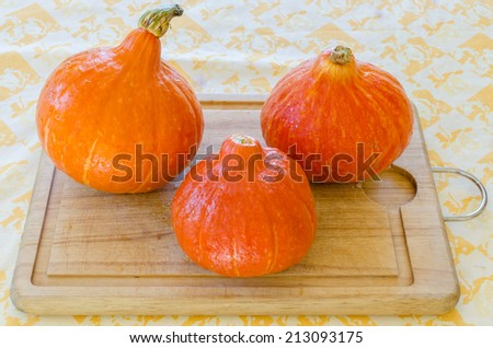 Threee red pumkins on wood board - stock photo