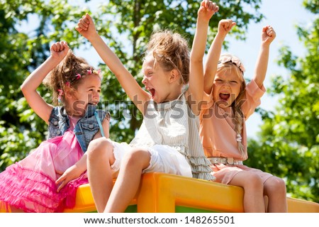 Threesome girl friends raising hands together and shouting in park. - stock photo
