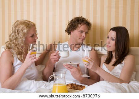 Threesome having a breakfast in bed - stock photo
