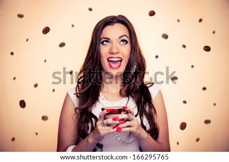 Thrilled beautiful brunette holding cup of coffee while coffee beans falling around her, with beige background - stock photo