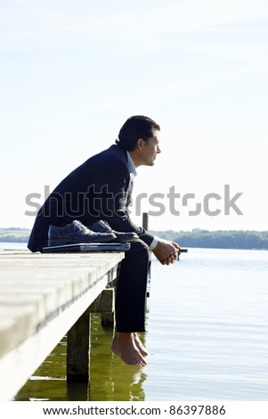 Thrilled businessman running on a jetty - stock photo