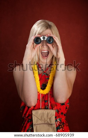 Thrilled female tourist looking through binoculars on a red background - stock photo