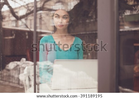 Through glass beautiful woman is working with her laptop