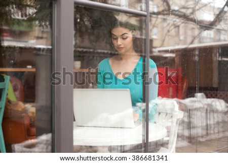 Through glass woman is working with her grey laptop