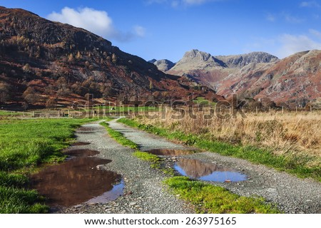 Through the puddles to the pikes. In this lovely view a few puddles lie in the path towards the magnificent Langdale Pikes. - stock photo