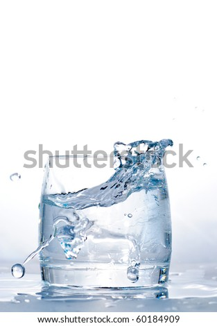 Throwed ice cube into the glass of water. - stock photo