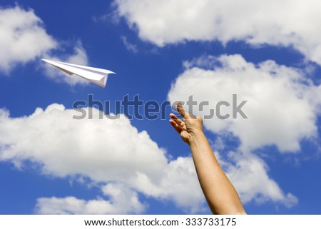 Throwing a paper airplane into the sky. - stock photo