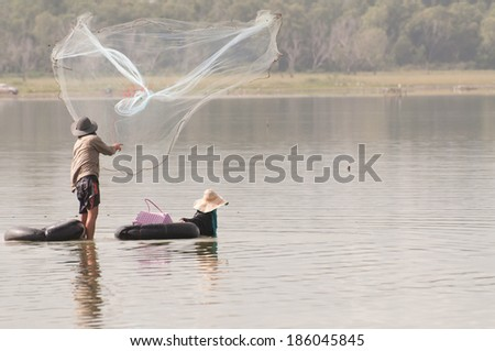 throwing fishing net during in thailand - stock photo