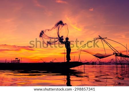 Throwing fishing net during sunrise, Thailand - stock photo