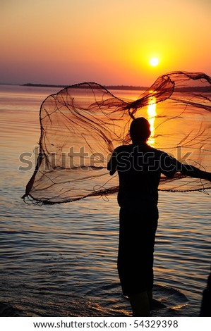 throwing fishing net during sunset - stock photo