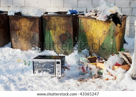 Thrown away microwave in snow near waste containers with garbage - stock photo