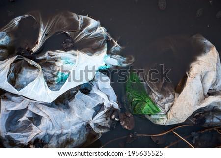 Thrown away plastic bags floating in black dirty water - stock photo