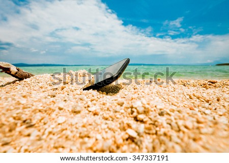Thrown, half buried in the sand of an ocean or sea shore sand smartphone. Nobody, blue sky with some clouds above. - stock photo