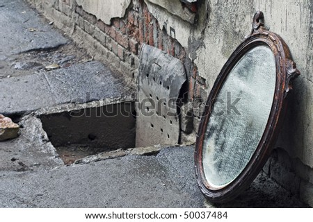 Thrown Out Old Mirror Standing Against Wall - stock photo