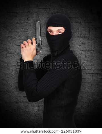 thug in mask and gun in his hand - stock photo