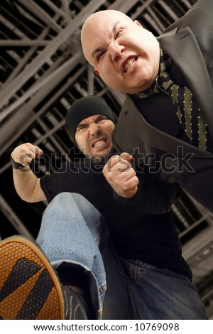 Thugs beating me while I'm down on the ground.  Slight motion on the arms and hands.  Focus is on the left attackers face. - stock photo