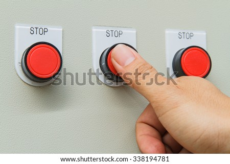 Thumb touch on red stop switch on control panel for machine control - stock photo