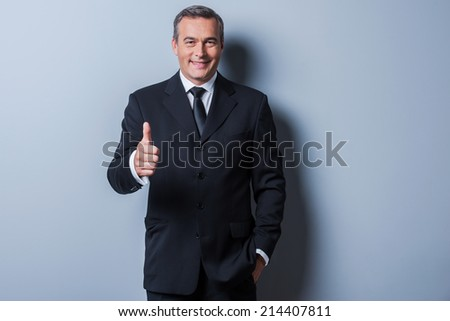 Thumb up for success! Cheerful mature man in formalwear showing his thumb up and smiling while standing against grey background - stock photo