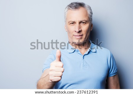 Thumb up for success! Cheerful senior man in casual showing his thumb up and smiling while standing against grey background - stock photo