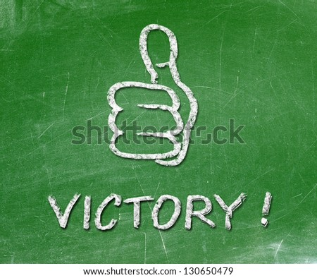 Thumb up sign drawn with chalk on a blackboard. Text written in chalk victory