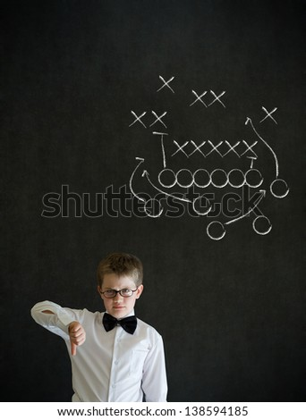 Thumbs down boy dressed up as business man with chalk American football strategy on blackboard background - stock photo