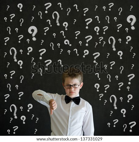 Thumbs down boy dressed up as business man with chalk questions marks on blackboard background - stock photo