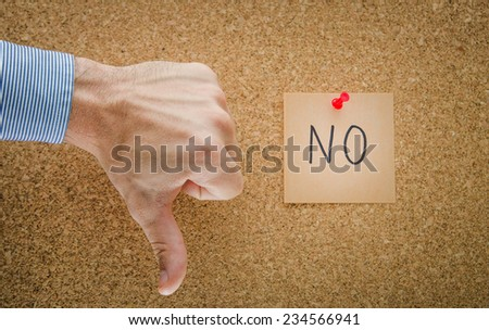 Thumbs down with a pinned red paper note with NO written and a business man hand showing refusal and denial with a contrast strong light suggesting a serious look - stock photo