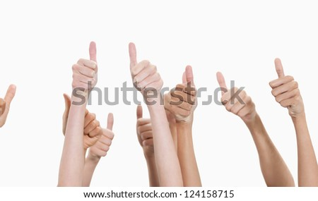 Thumbs raised and hands up against white background - stock photo