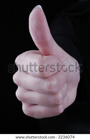 Thumbs up against black background - stock photo