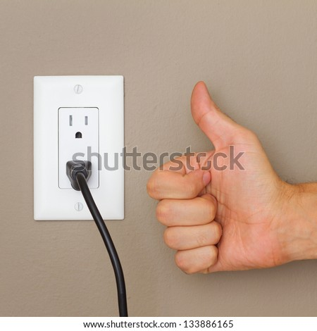 Thumbs up, and Electric cable in Electrical Outlet on the Wall. Power 110v - stock photo