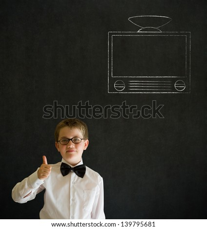Thumbs up boy dressed up as business man with chalk tv television on blackboard background - stock photo