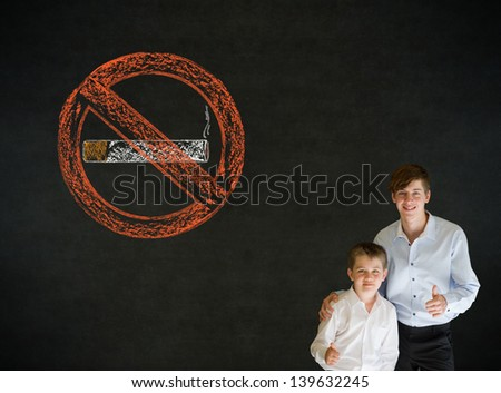 Thumbs up boy dressed up as business man with no smoking chalk sign on blackboard background - stock photo