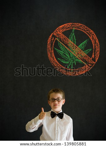 Thumbs up boy dressed up as business man with no weed marijuana on blackboard background - stock photo