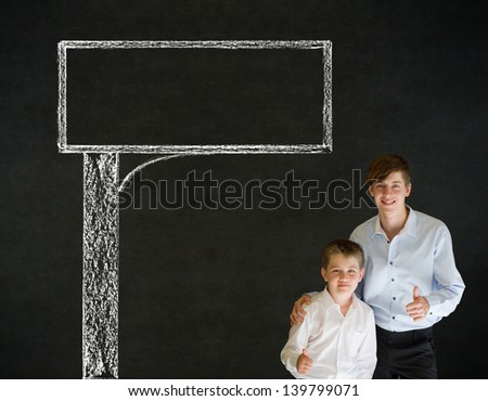 Thumbs up boy dressed up as business man with teacher man and chalk road advertising sign on blackboard background - stock photo