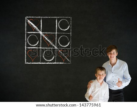 Thumbs up boy dressed up as business man with teacher man and chalk tic tac toe love valentine concept on blackboard background - stock photo