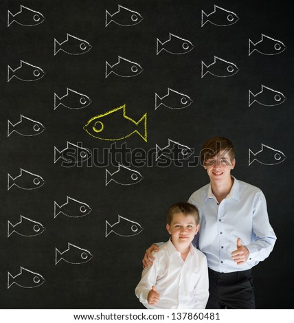 Thumbs up boy dressed up as business man with teacher man and independent thinking chalk fish swimming against the flow on blackboard background - stock photo