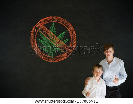 Thumbs up boy dressed up as business man with teacher man and no weed marijuana on blackboard background - stock photo