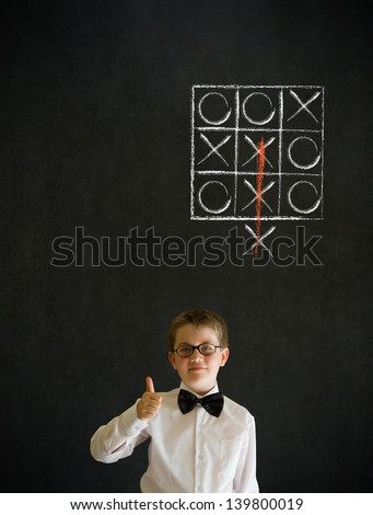 Thumbs up boy dressed up as business man with thinking out of the box tic tac toe concept on blackboard background - stock photo