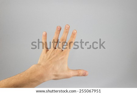 thumbs up. Closeup of male hand showing thumbs up sign against white background, Hand with two fingers up in the peace or victory symbol. Also the sign for the letter V in sign language. - stock photo