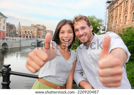 Thumbs up couple happy in Stockholm, Sweden. Excited people giving thumbs up gesture looking at camera. Multiracial young couple walking outside in Stockholm. Scandinavian man, Asian woman.