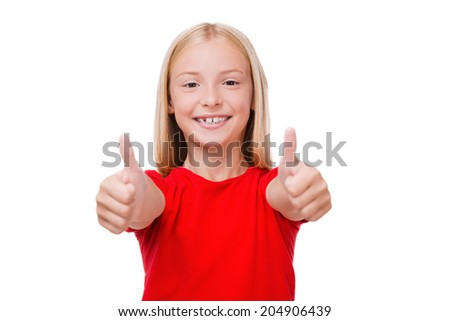 Thumbs up! Cute little girl showing her thumbs up while standing isolated on white - stock photo