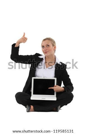 Thumbs up from a businesswoman for the blank screen on her laptop - stock photo