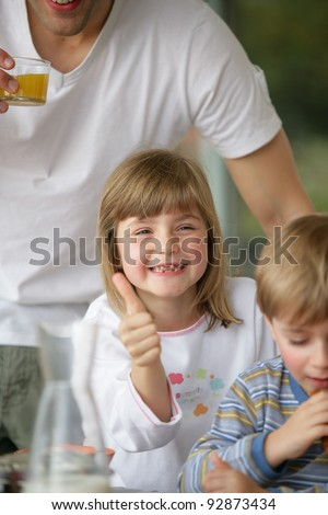 Thumbs up from a young girl at breakfast - stock photo