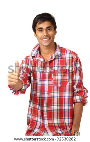 Thumbs up gesture by cute smiling guy - stock photo